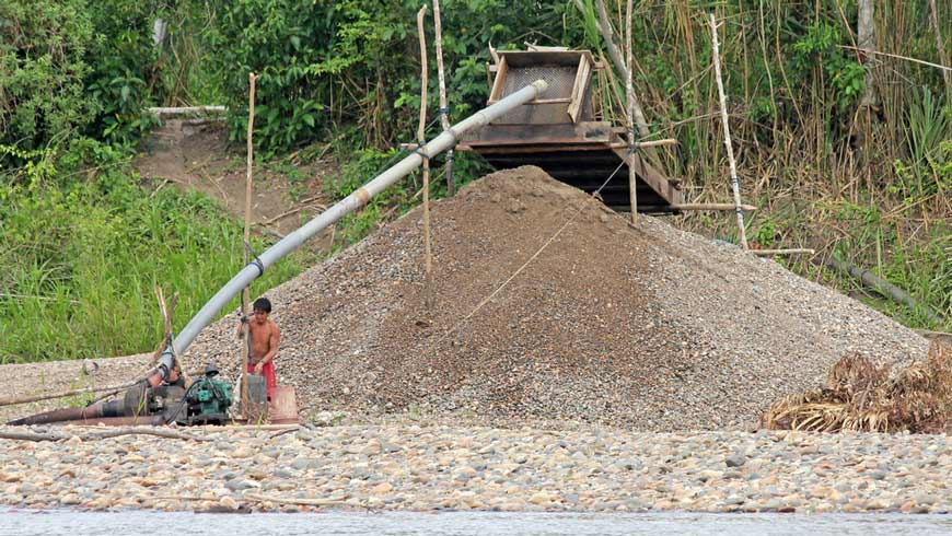 Small-scale gold miner next to tailings pile in Peru