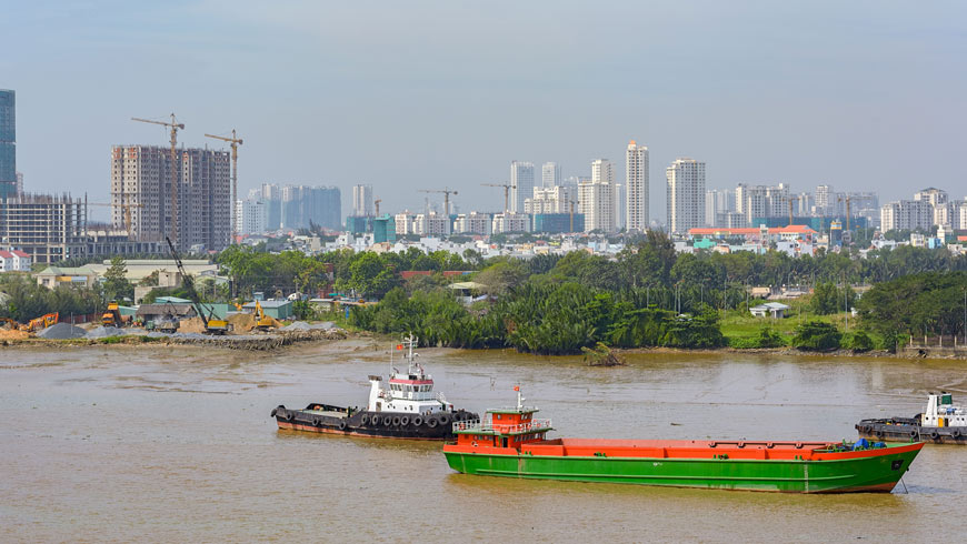 Ho Chi Minh City scene with river in foreground and various construction on high-rise buildings in background