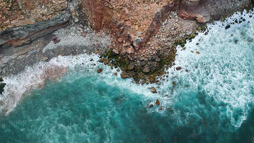 Aerial top view of sea waves hitting rocks on the beach with turquoise sea water.