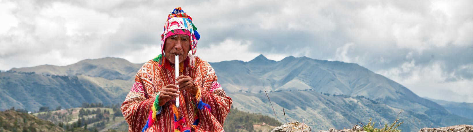 Peruvian indigenous man playing flute in mountains