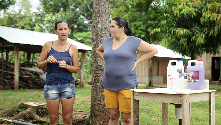 Two women standing next to a water station in Costa Rica