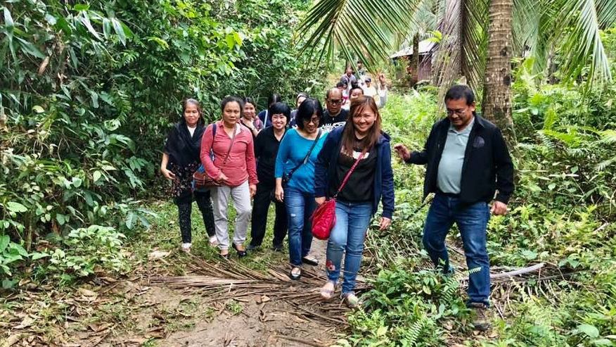 Anna Teh walking with people on a project site visit to a coastal community in Siargao Island