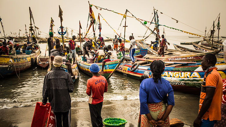 Artisanal fishing port of Koukoude, prefecture of Boffa, Guinea. Fish sellers wait on the shore for the fishermen to come back with the fish they collected