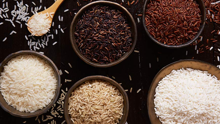 Different types of rice in bowls on a rustic table.
