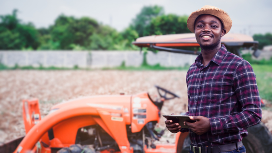 African farmer is using a tablet on the background of working tractor with a cultivator in the field