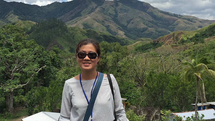 Seo-Jeong Yoon in front of a mountain and forest landscape in Navilawa village in Fiji