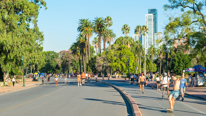 People enjoying outdoor activities on a palm tree lined street in Buenos Aires, Argentina