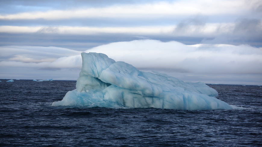 Tilted iceberg in open ocean.