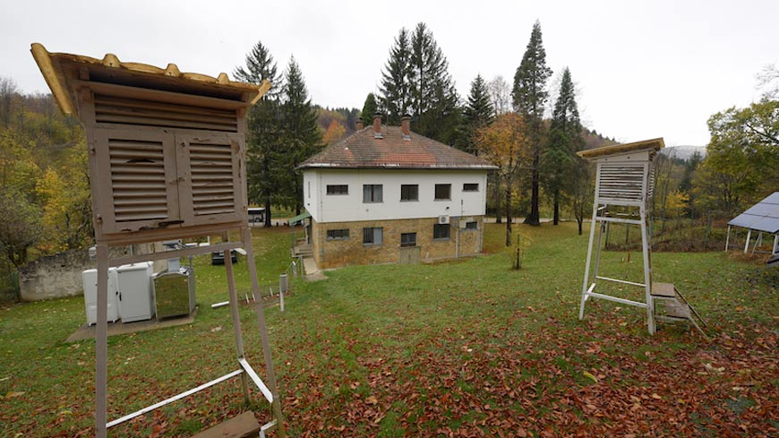 House in forested valley with two air quality monitoring stations in foreground