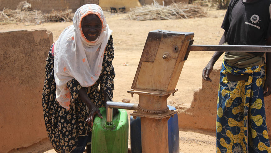 Woman pumping water in Burkina Faso