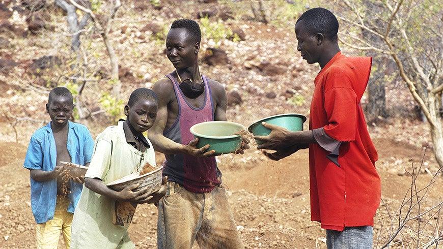 Children pan for gold against an arid backdrop in Burkina Faso.