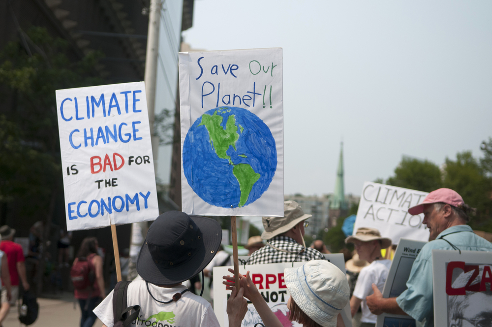 Protesters with signs urging to save the planet with climate control. July, 2015, Toronto, Canada.