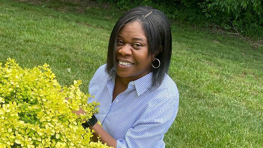 Woman crouching by a bush