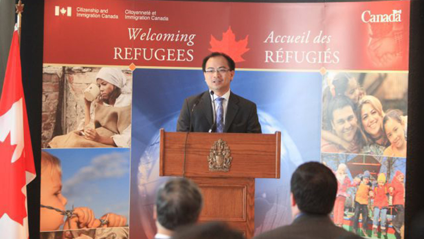 Tom Bui speaks in front of an audience at a World Refugee Day event in Canada