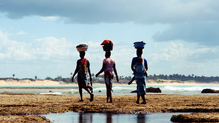 Women in Mozambique walking near the ocean