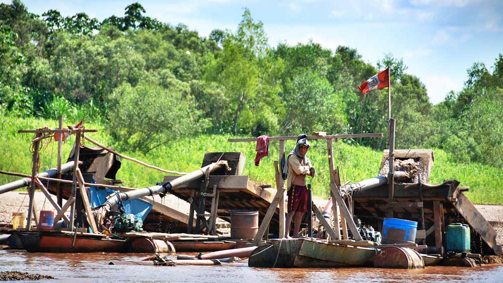 Illegal gold mining operation on small jungle river in Peru