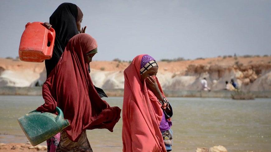 Women gathering water near sand dam