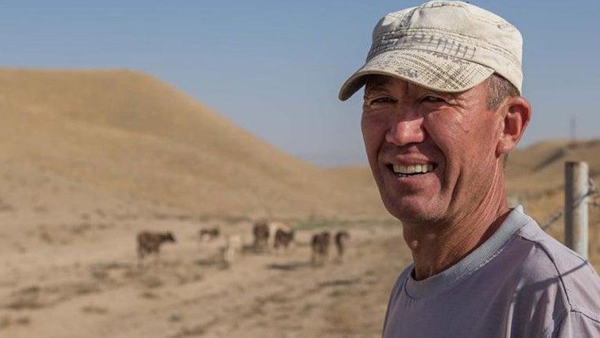Farmer standing alongside herd in arid, mountainous area of Tajikistan