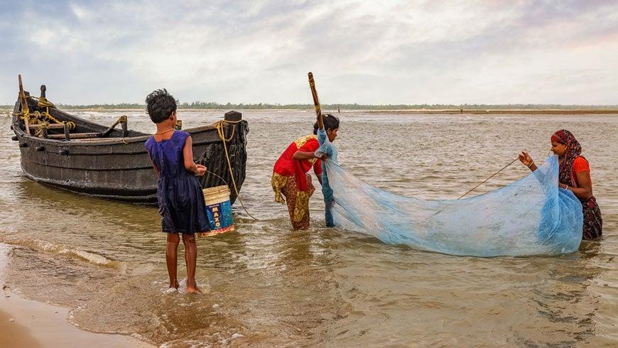 Women tending a net near the seashore.