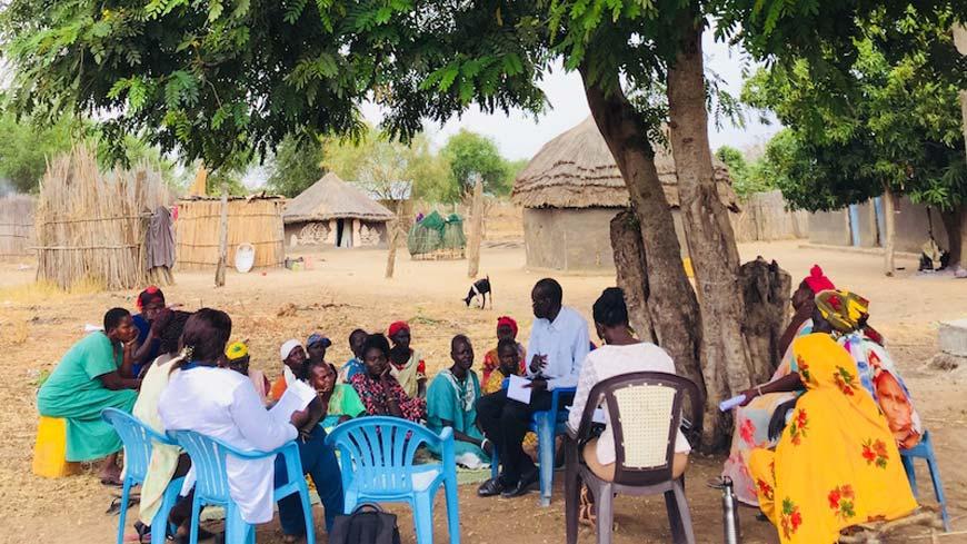 Women gathering under a tree near a village in South Sudan.