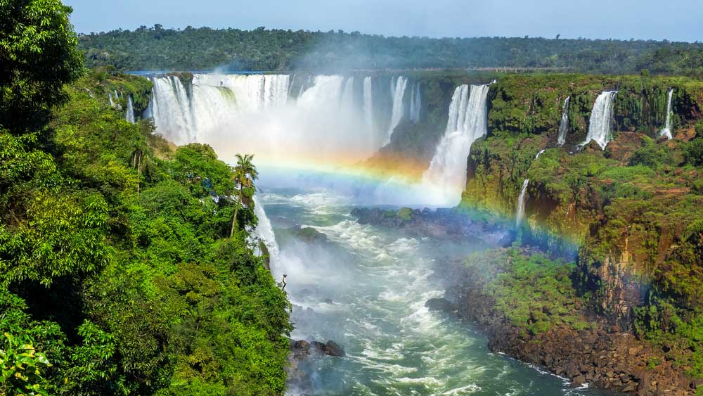 Iguazu Falls on the border of Brazil, Argentina, and Paraguay with rainbow in foreground