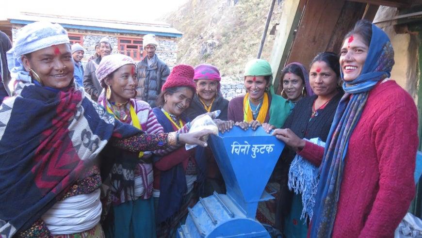 Nepalese women stand around a millet machine