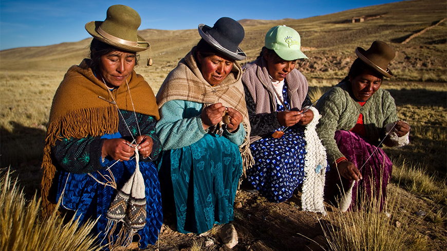 Peruvian women using alpaca fiber to knit handmade goods