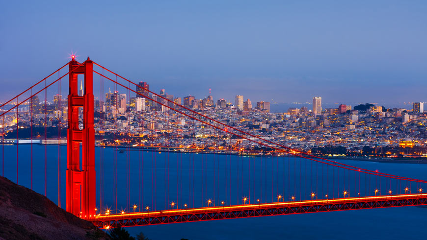 Golden Gate Bridge in foreground at dusk with San Francisco in background.