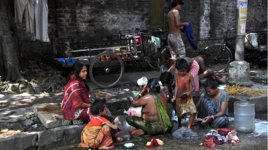 Local people wash themselves on the street of Kolkata on October 27, 2009. Homeless living on the street are common in every city of India.