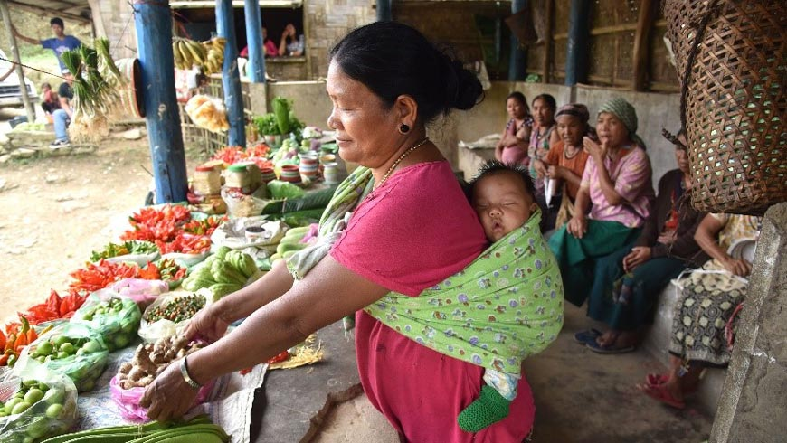Woman tending to vegetables with a sleeping baby on her back. Photo: UNDP India.