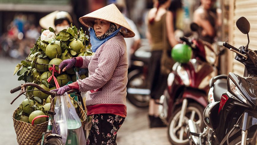 A Vietnamese woman sells coconuts on a street in Ho Chi Minh City (Saigon) at sunset. Photo: DenisShumov/Shutterstock.