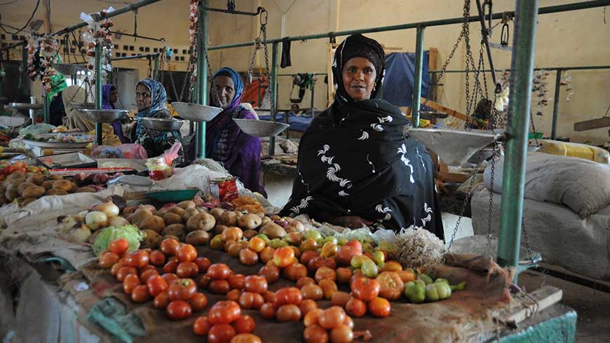 Women selling local produce at a market. Photo: Shutterstock.