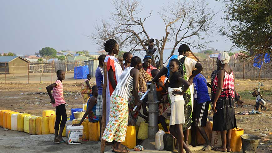 People lining up to get water from a borehole. Photo: Shutterstock.