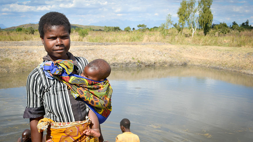Woman and child near a fish farm in Malawi