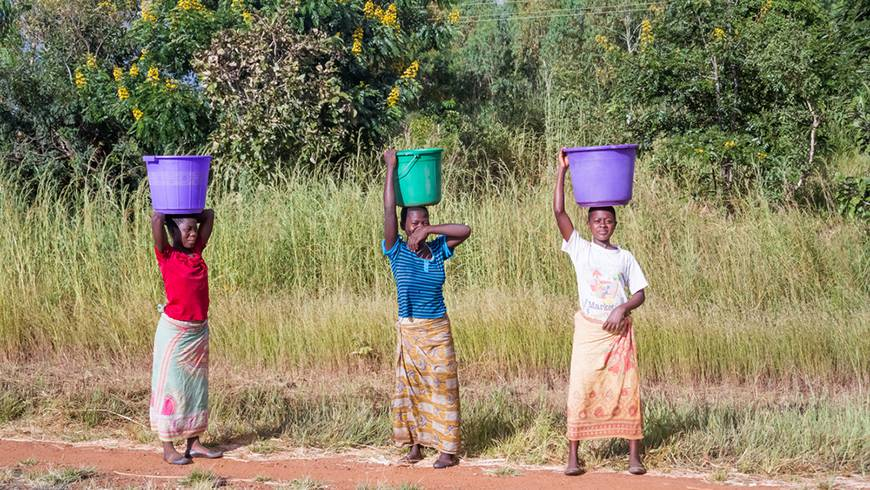 Three women carrying buckets on their heads and walking by the road near Kasungu in Malawi.