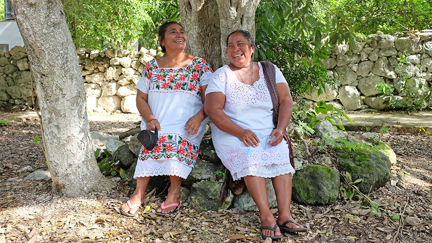 Mexican women rest against a tree