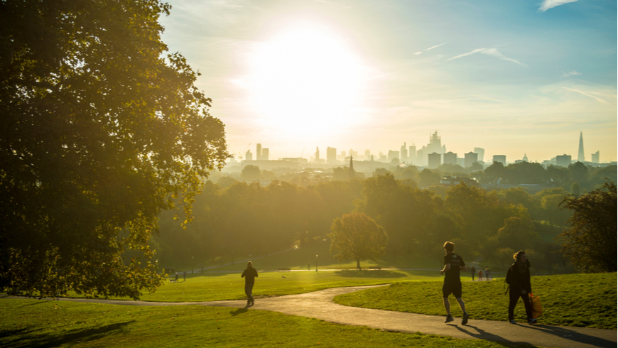 Joggers run through a park near London at sunrise