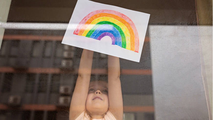 Girl displays her painting of a rainbow in the window