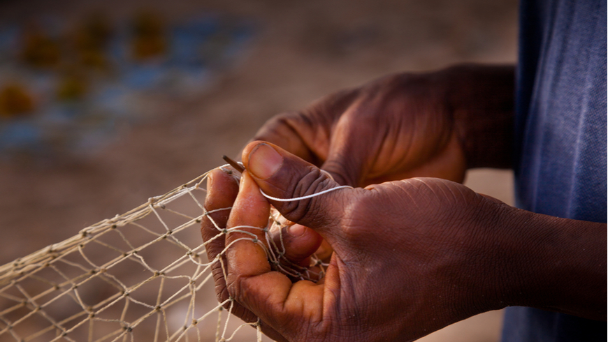 A person tying a fishing net in Sierra Leone