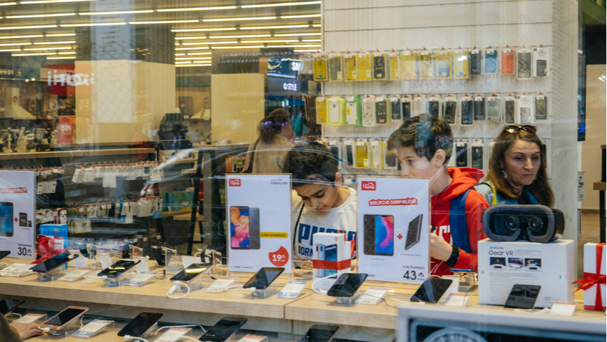 View from the street of young boys using electronics technology products inside modern supermarket tech store on main Baku avenue