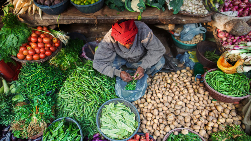 A man surrounded by vegetables and greens at his place at Indian Bazaar. A mix of colors and textures. Captured in India, Uttar Pradesh, Varanasi.