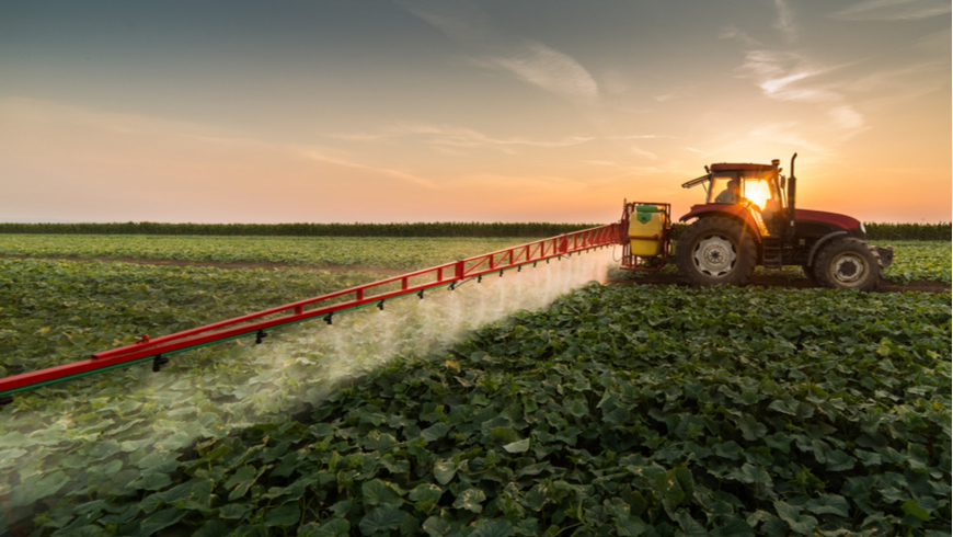 Tractor spraying pesticides on vegetable field with sprayer at spring. Photo: Fotokostic/Shutterstock.