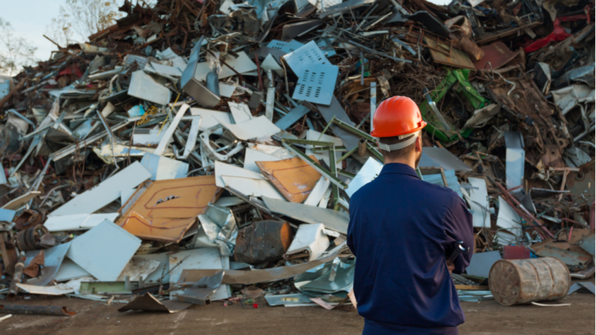 Man looking at piles of rubbish at a landfill. Photo: Comaniciu Dan/Shutterstock.