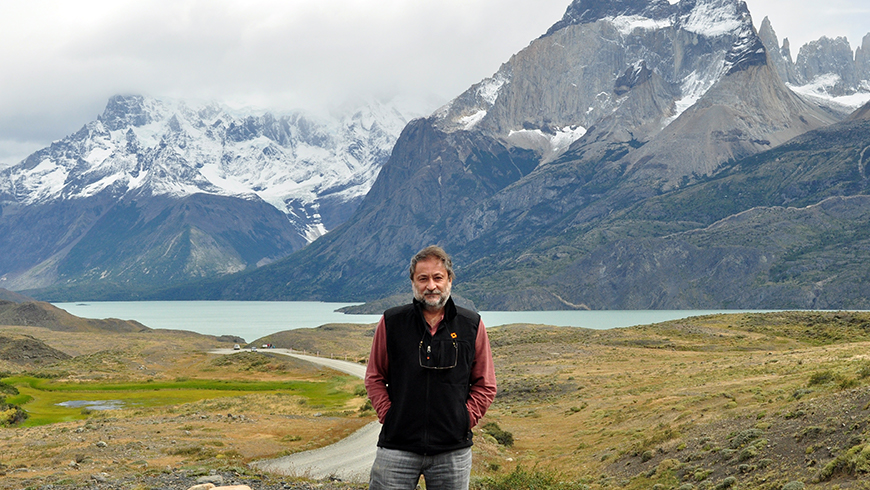 Miguel Stutzin stands in front of a mountainous landscape in Torres del Paine National Park, Chile