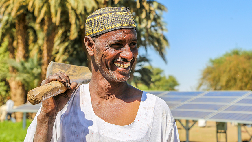 Sudanese man in front of solar panels