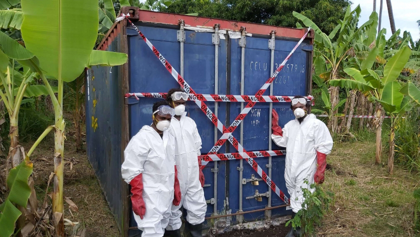 Men in HAZMAT suits in front of a shipping container full of DDT